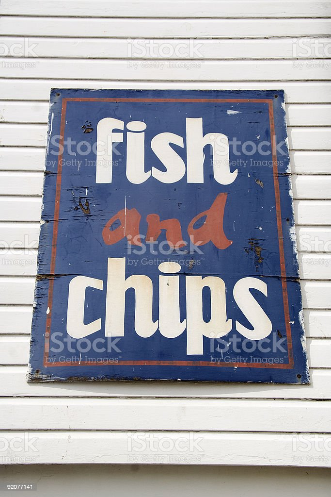 Weathered fish and chips sign at seaside royalty-free stock photo