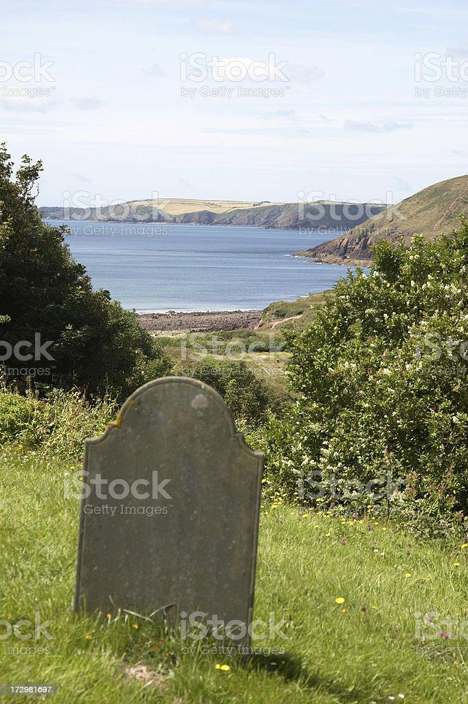 Weathered gravestone and sea background stock photo