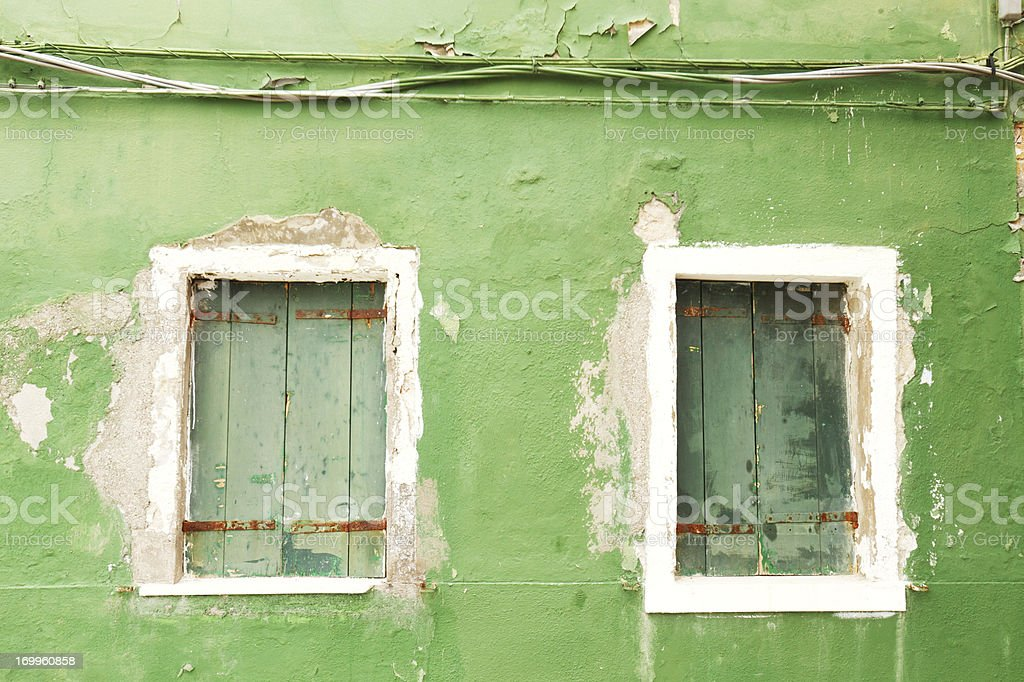 Weathered green facade with windows and wires royalty-free stock photo