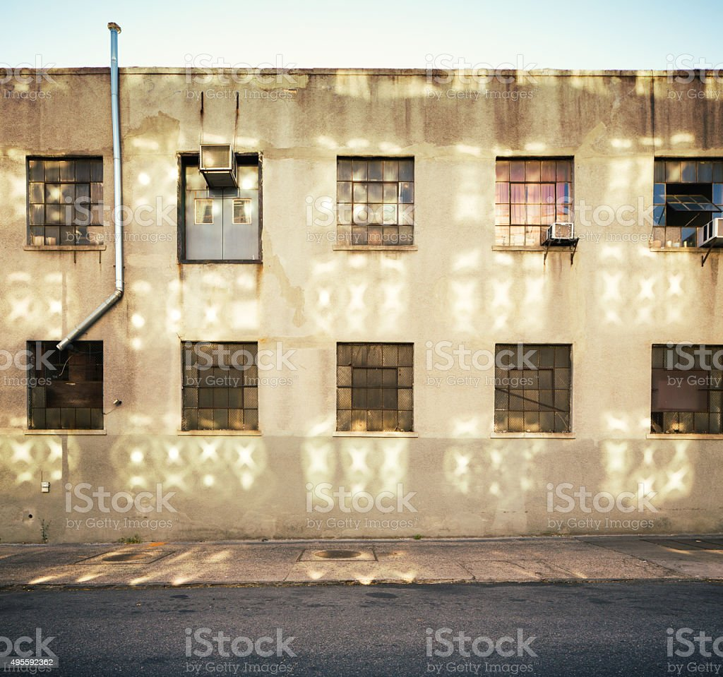 Weathered industrial building with window reflections stock photo