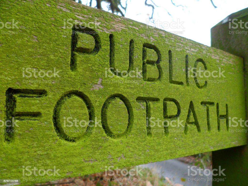 Weathered old carved wooden 'Public Footpath' sign stock photo