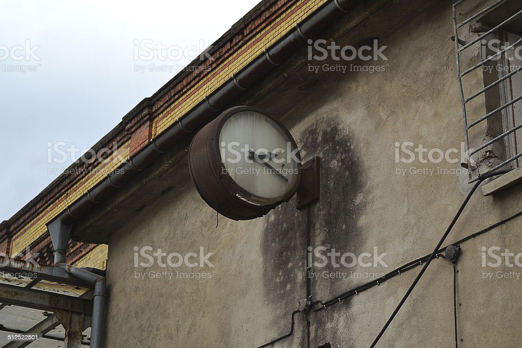 Weathered old wall clock at industrial building stock photo