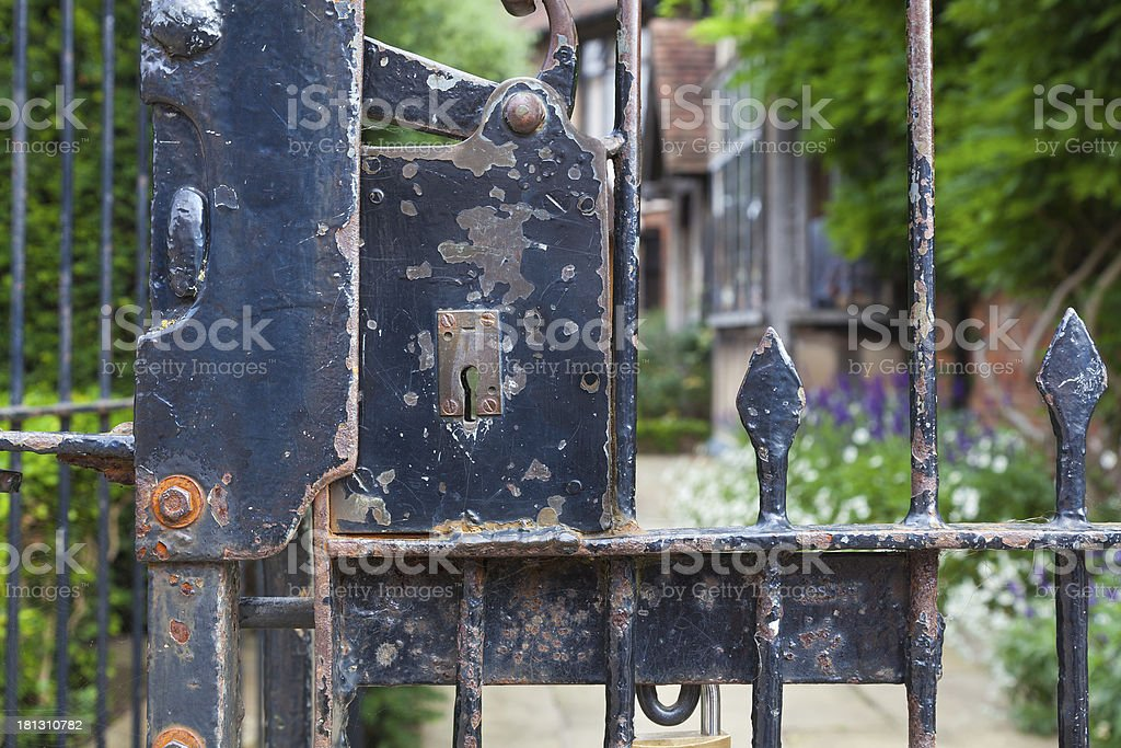 Weathered ornate wrought iron gate with lock. royalty-free stock photo