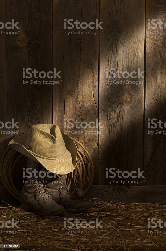 Weathered packer's boots,hat & rope on barn floor-sunbeam on barnwood wall royalty-free stock photo