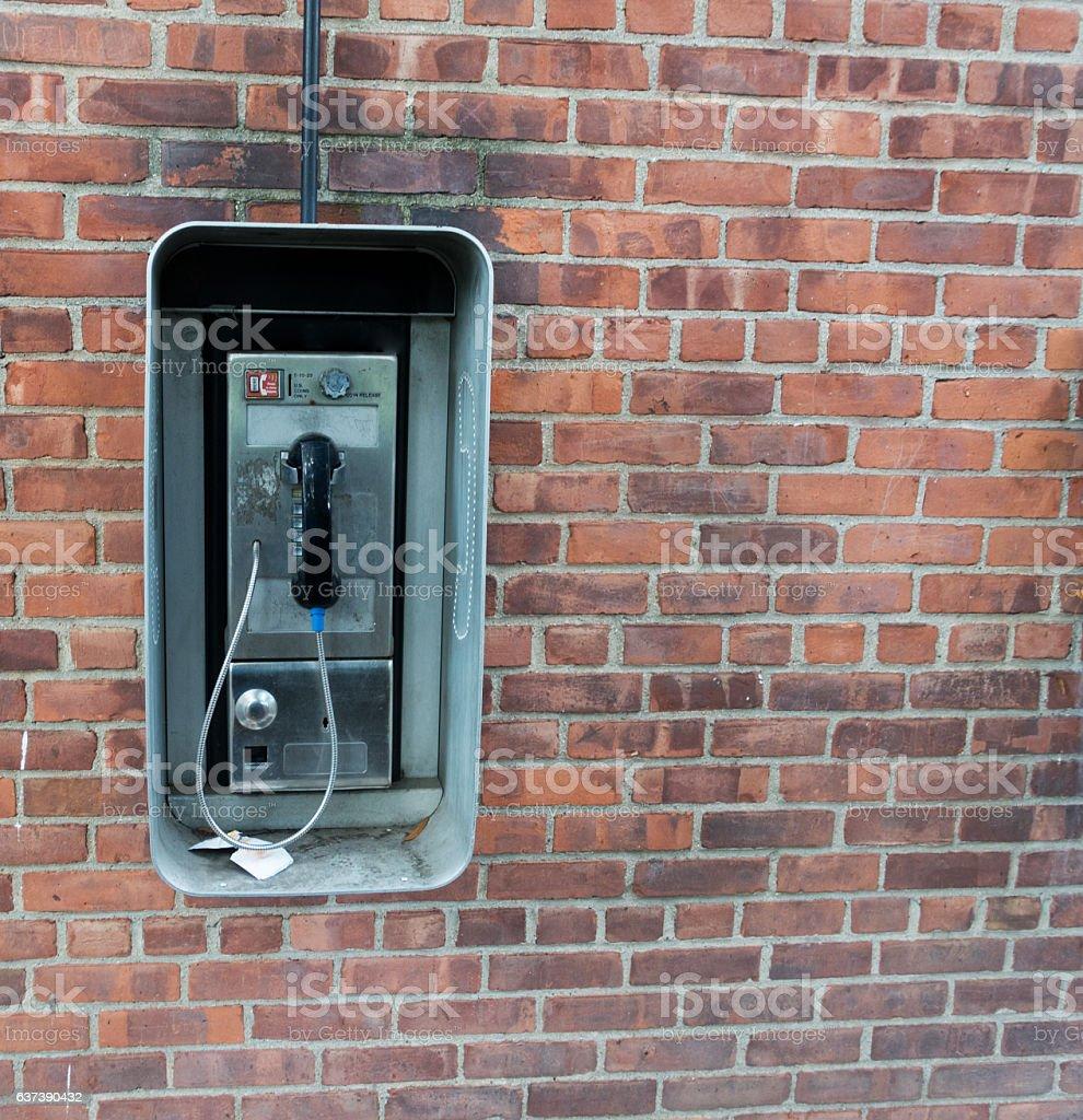 Weathered Pay Phone on Brick Wall stock photo