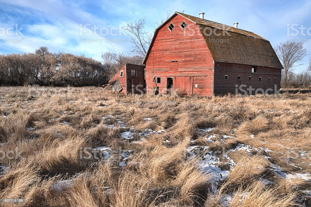 Weathered Red Barn in Abandoned Farmyard stock photo
