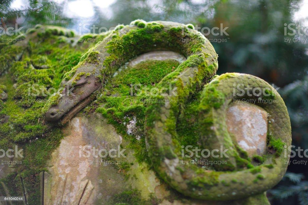 Weathered snake head on Melaten Graveyard stock photo