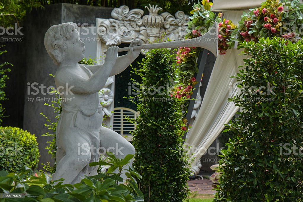 Weathered statue of an infant angel in garden stock photo