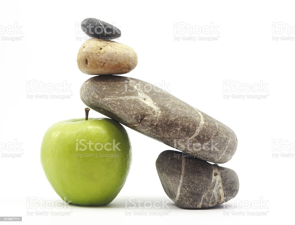 Weathered stones stacked on and against an apple royalty-free stock photo