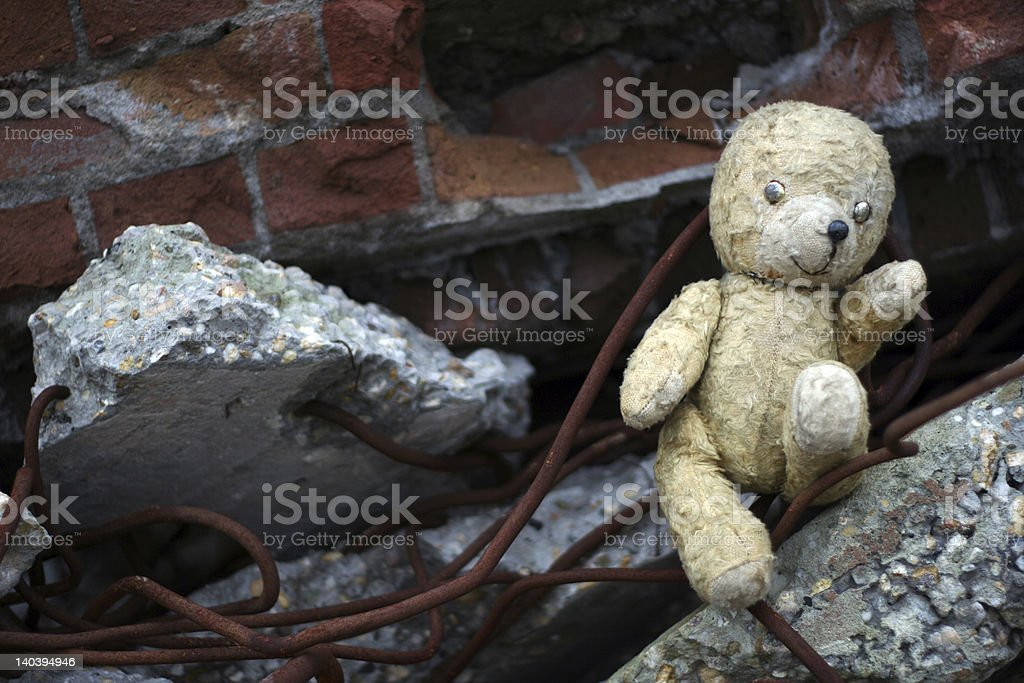 Weathered teddy bear in a pile of concrete rubble stock photo