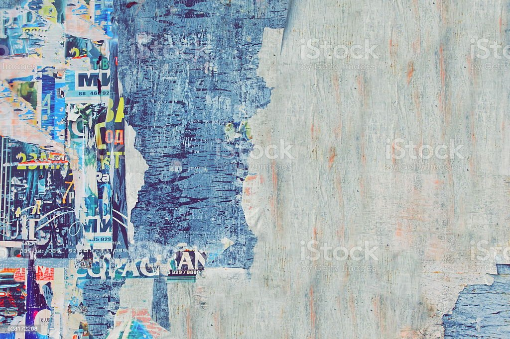 Weathered Torn Color Posters On The Old Wood Billboard Backgroun stock photo
