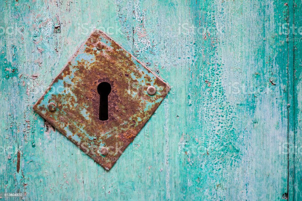 Weathered Turquoise Door with Rusty Antique Keyhole (Close-Up) stock photo