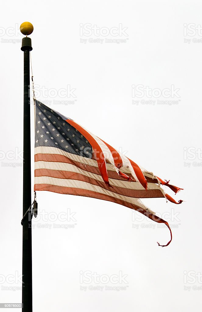 Weathered USA flag at half mast on a windy day stock photo