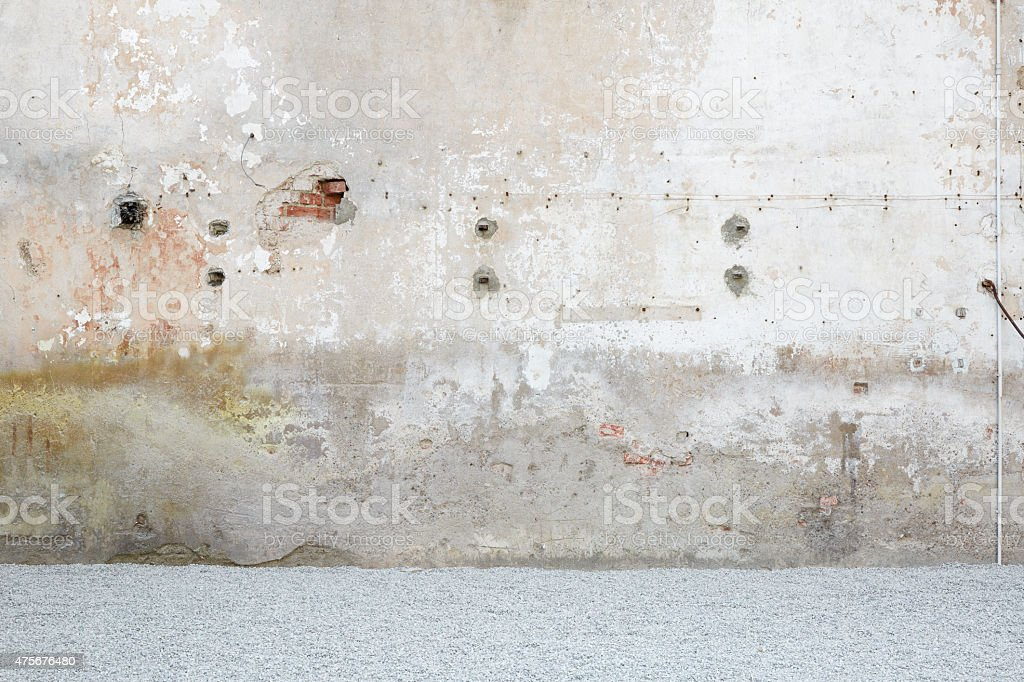 Weathered wall with gravel, stone chippings floor stock photo