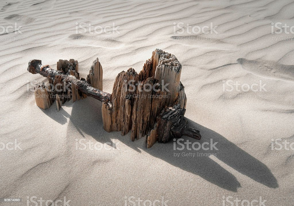 Weathered wooden groyne and rusty bolt on a sandy beach royalty-free stock photo