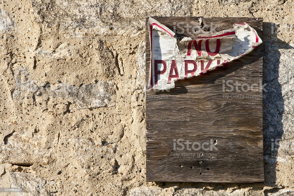 Weathered wooden plank 'No Parking' Sign on Wall stock photo