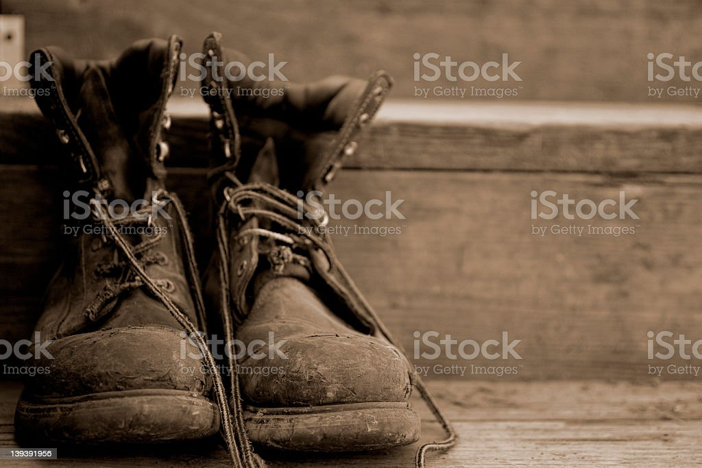 Weathered work boots on wooden steps stock photo