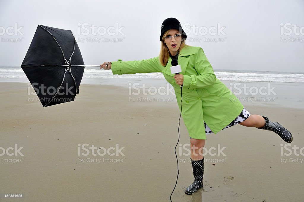 Weathergirl with Umbrella Being Blown Away stock photo