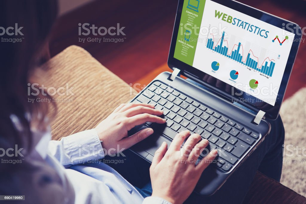 Web statistics consulting. Woman using a laptop computer to analyze web statistics. stock photo