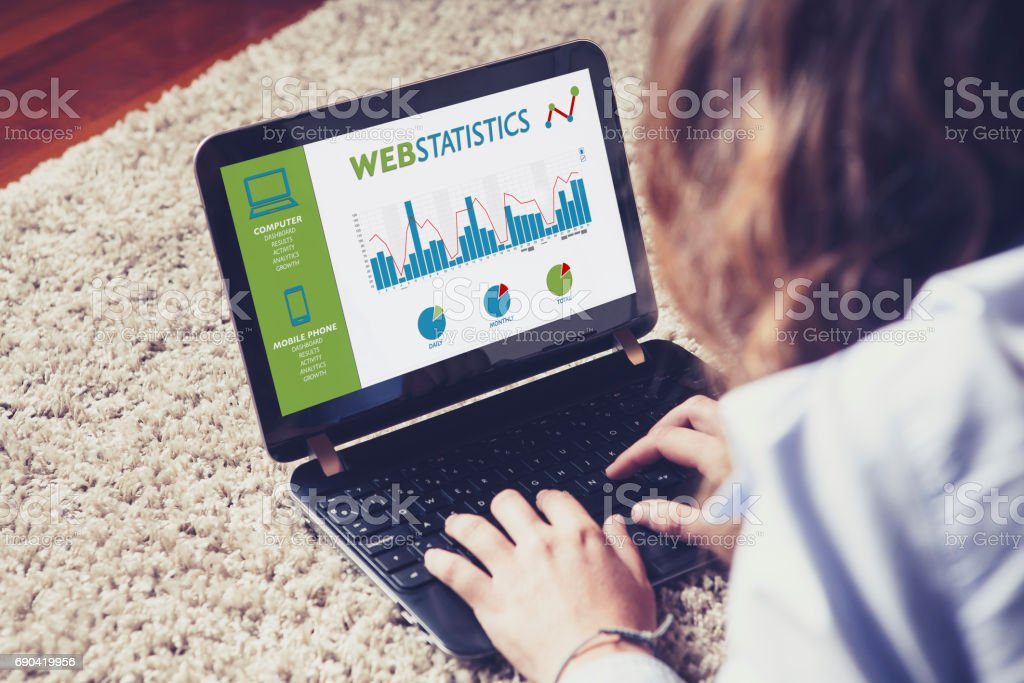 Web statistics in a laptop computer screen. Woman analyzing web traffic. stock photo