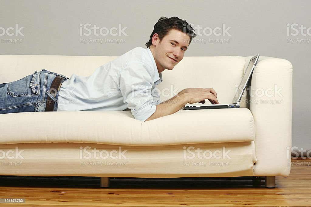 Web surfing on the couch with a smile royalty-free stock photo