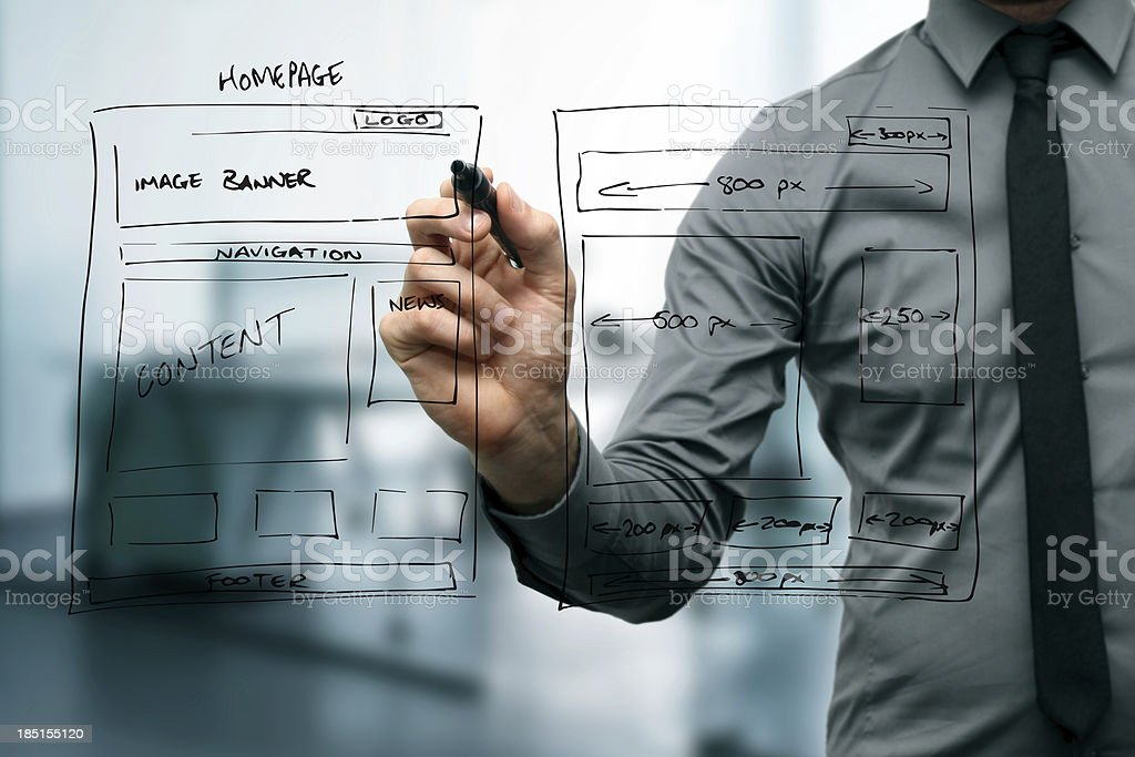 Website designer sketching wireframe plan on glass stock photo
