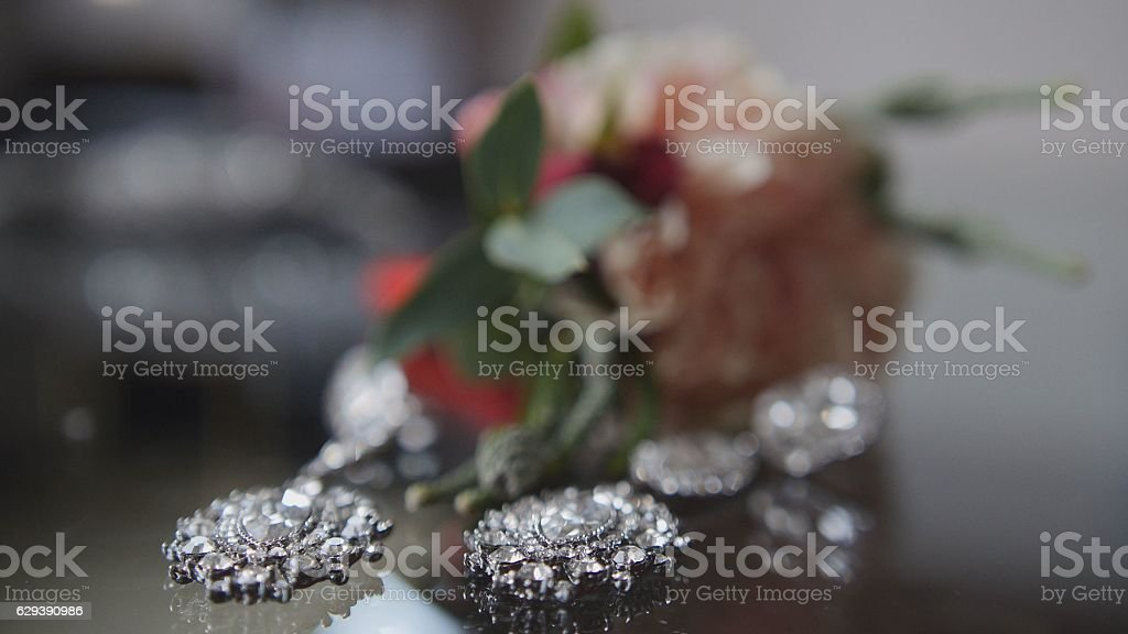 Wedding accessories on the table - silver earrings stock photo