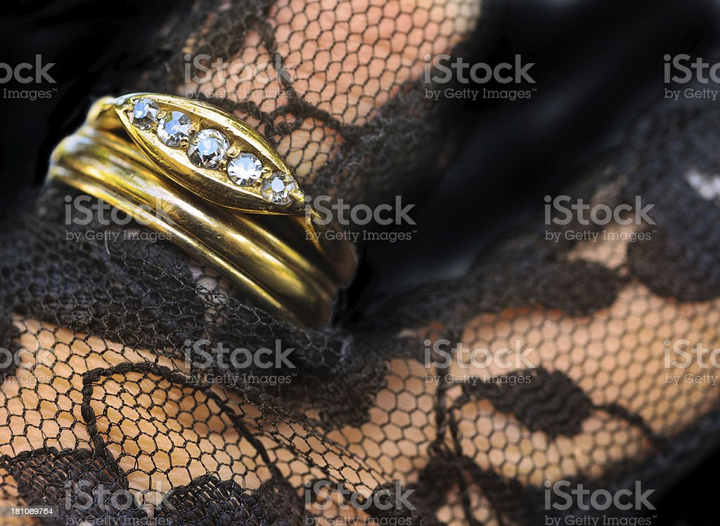 Wedding and engagement rings on black lace stock photo