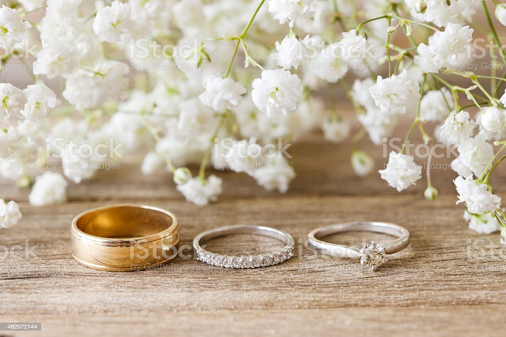 Wedding Bands & Engagement Ring on Rustic Timber Table stock photo