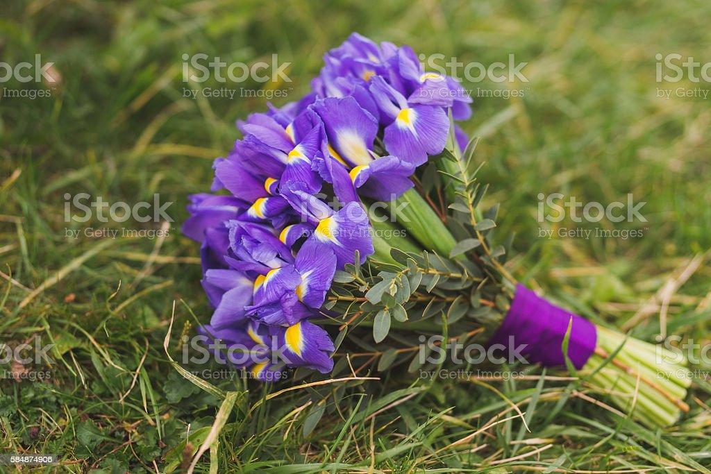 wedding bouquet of purple fleur-de-lis flowers outdoors on the grass stock photo