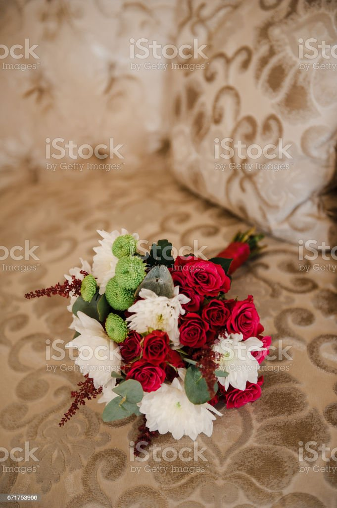 A wedding bouquet of roses and chrysanthemums on the sofa. stock photo