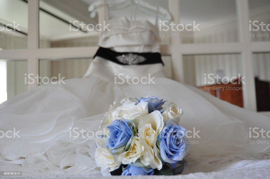 Wedding Bouquet on Bed with Wedding Dress on Mirror Headboard stock photo