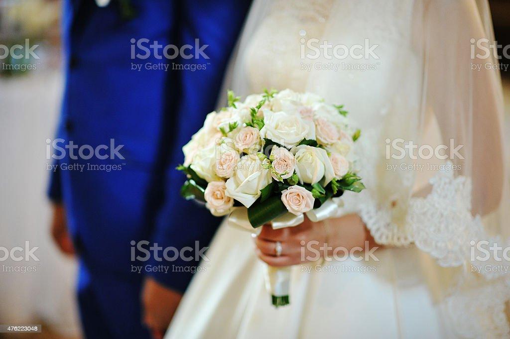 wedding bouquet on hands of bride stock photo