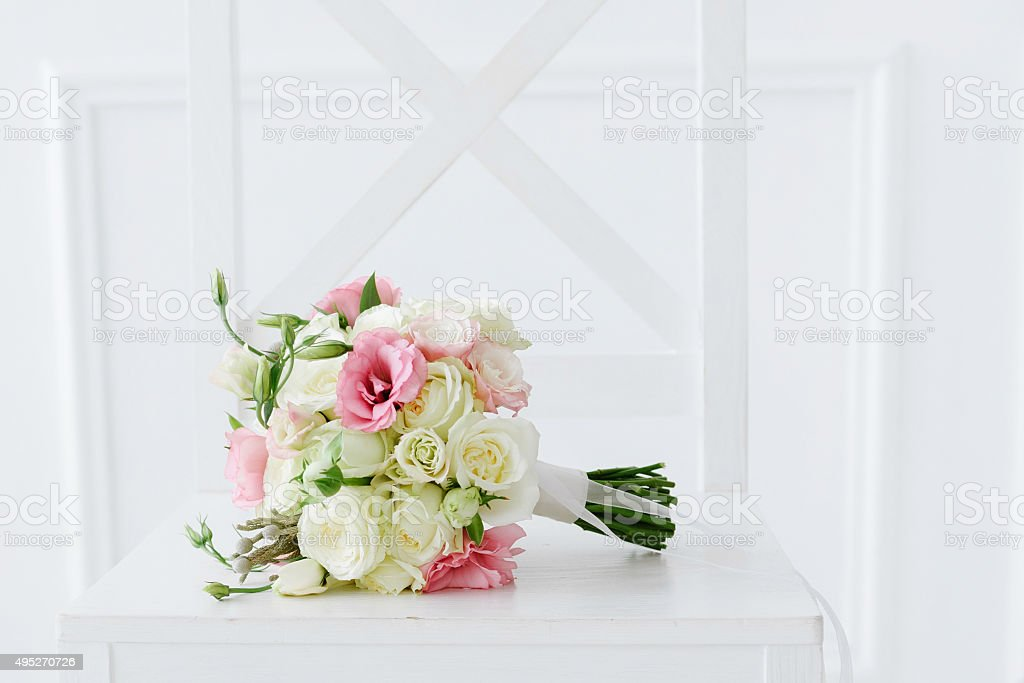 wedding bouquet on white chair stock photo