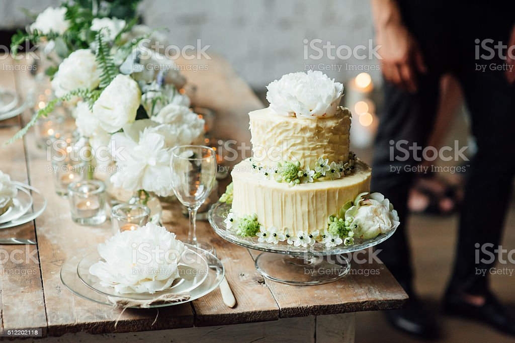 Wedding cake decorated loft style with a table and accessories stock photo