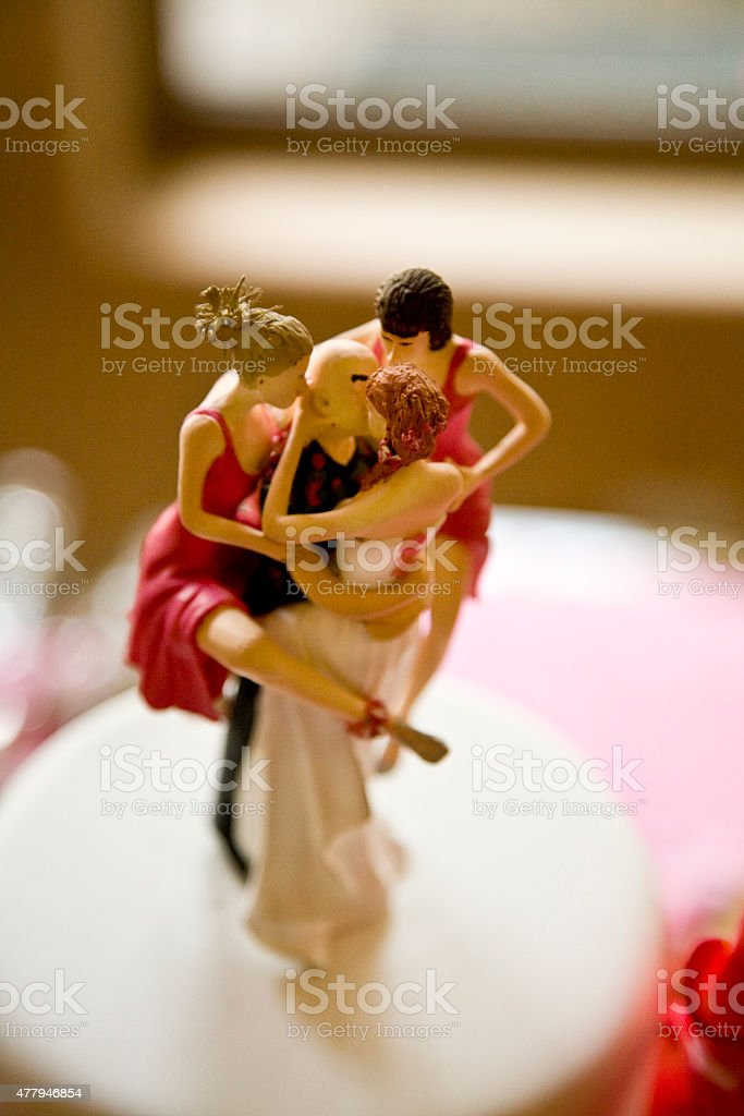 Wedding Cake Topper Depicting One Man with Several Women stock photo
