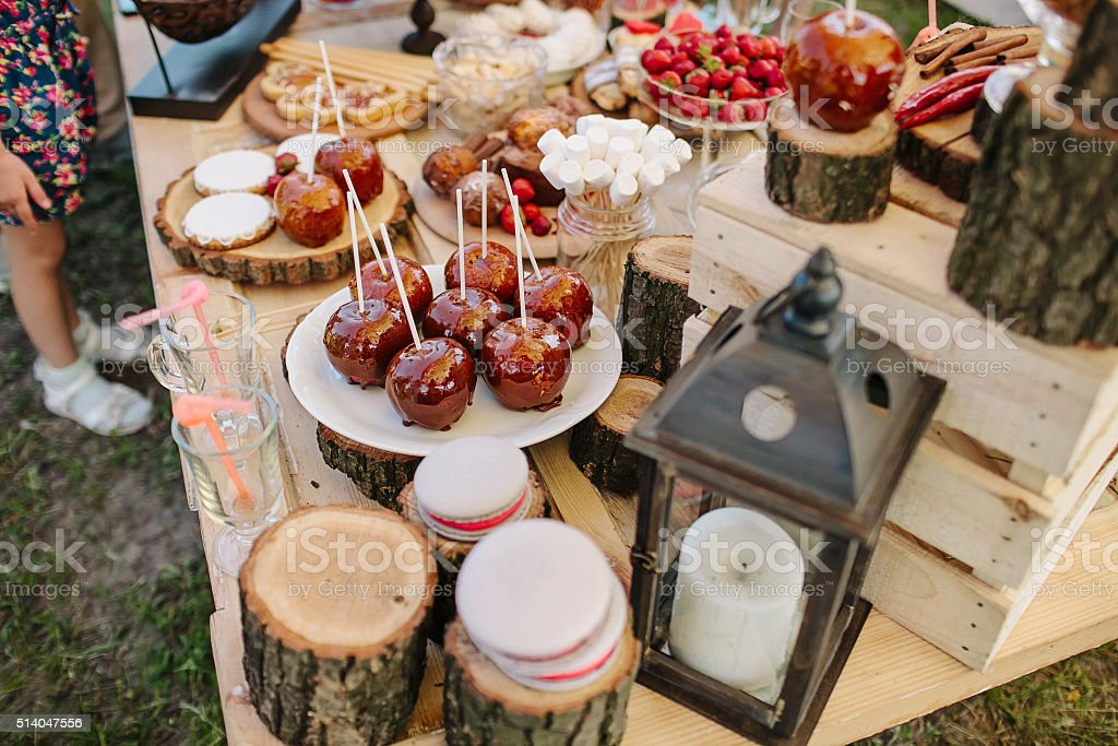 Wedding candy bar with caramel apples, fruits and macaroons stock photo