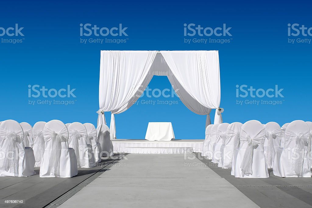 Wedding canopy with chairs, all in white on blue sky stock photo