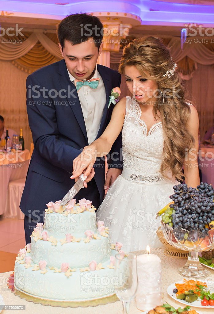 Wedding ceremony. Bride and groom cutting cake stock photo