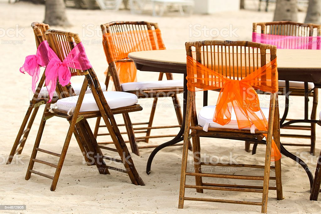 Wedding Chairs on the Beach with colorful chiffon ribbons attached stock photo