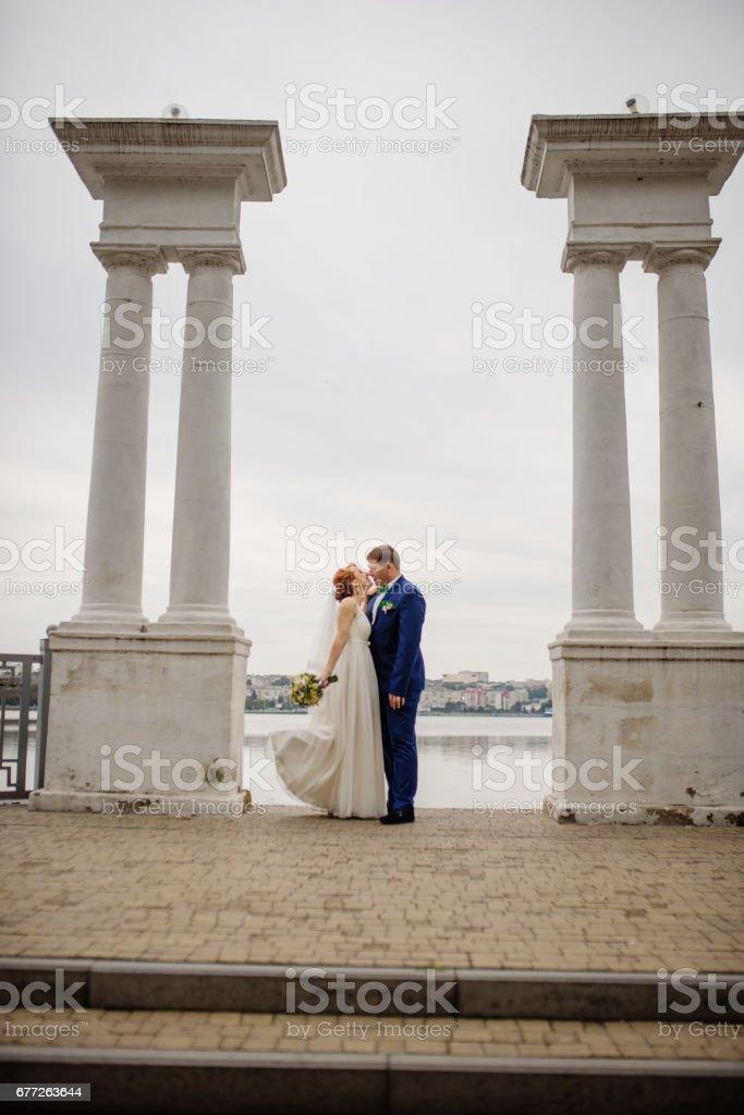 Wedding couple background two columns on lake. stock photo