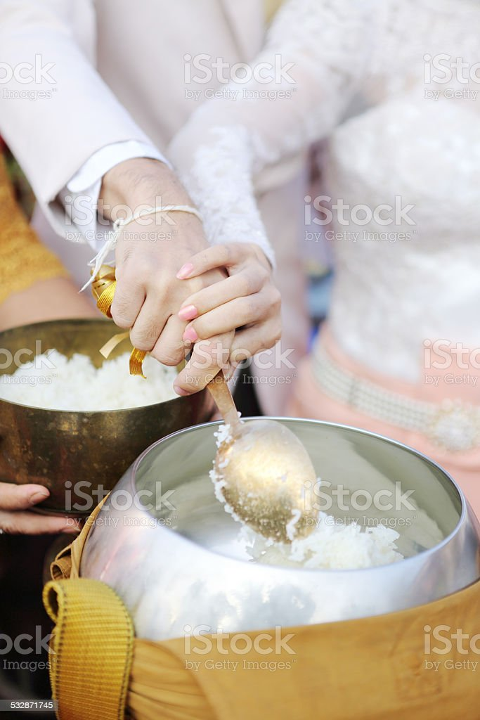 wedding couple  give alms to a Buddhist monk on morning stock photo