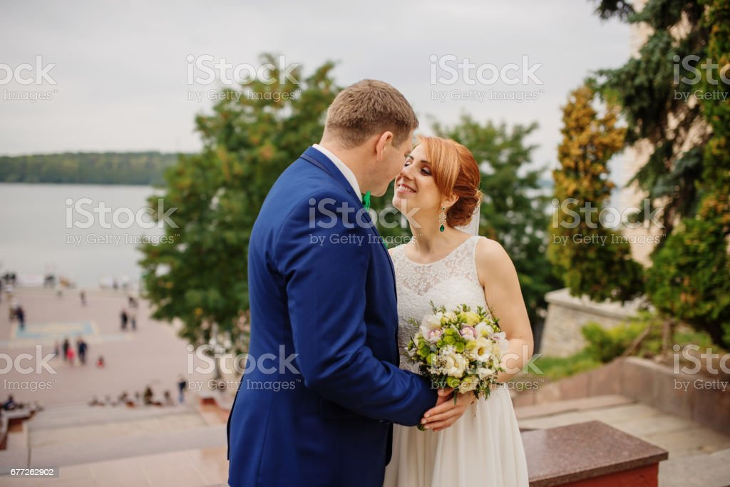 Wedding couple in love at cloudy day, walking on city. stock photo