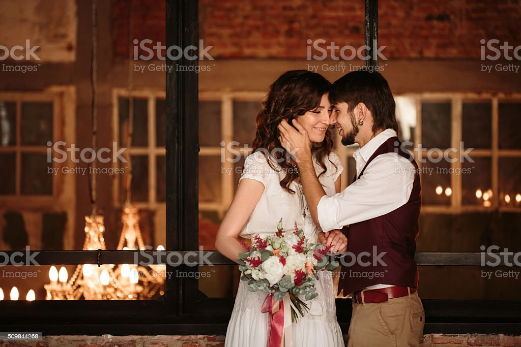 Wedding Couple Kissing in Loft Interior stock photo