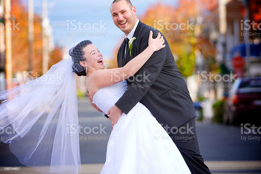 wedding couple laughing in the middle of  street royalty-free stock photo
