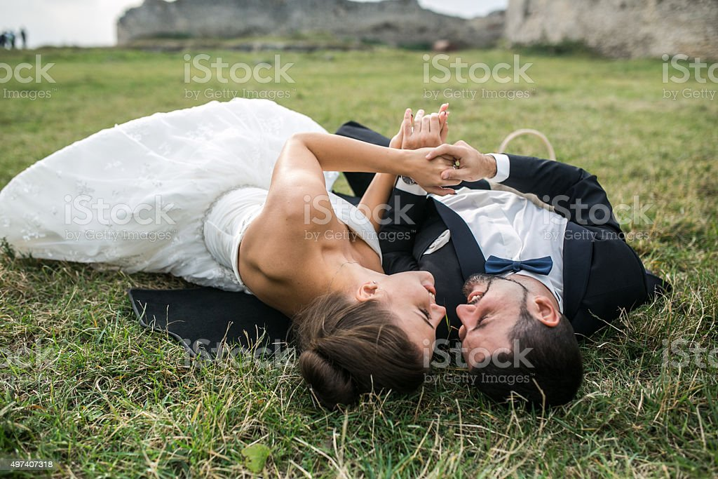 Wedding couple lying on the grass stock photo