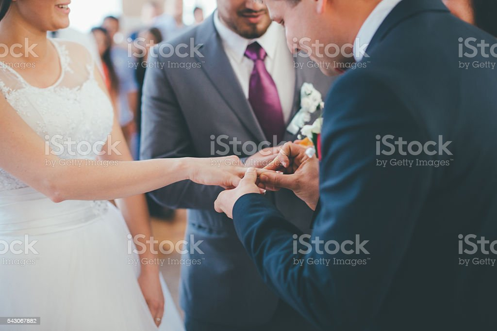 Wedding couple on their ceremony changing their wedding rings stock photo