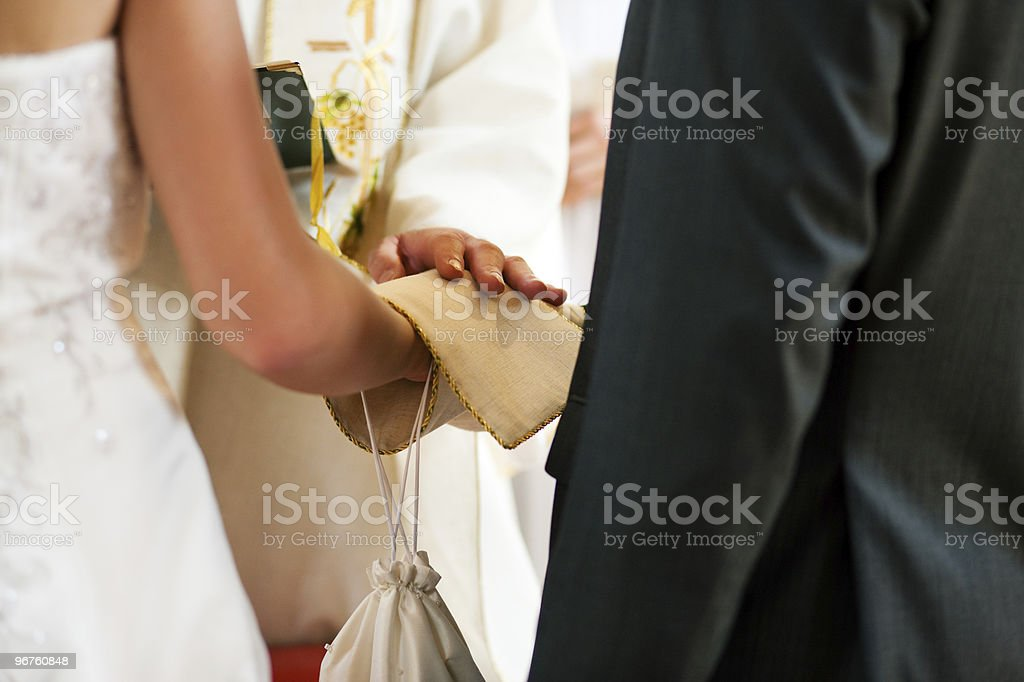 Wedding couple receiving blessing from priest stock photo