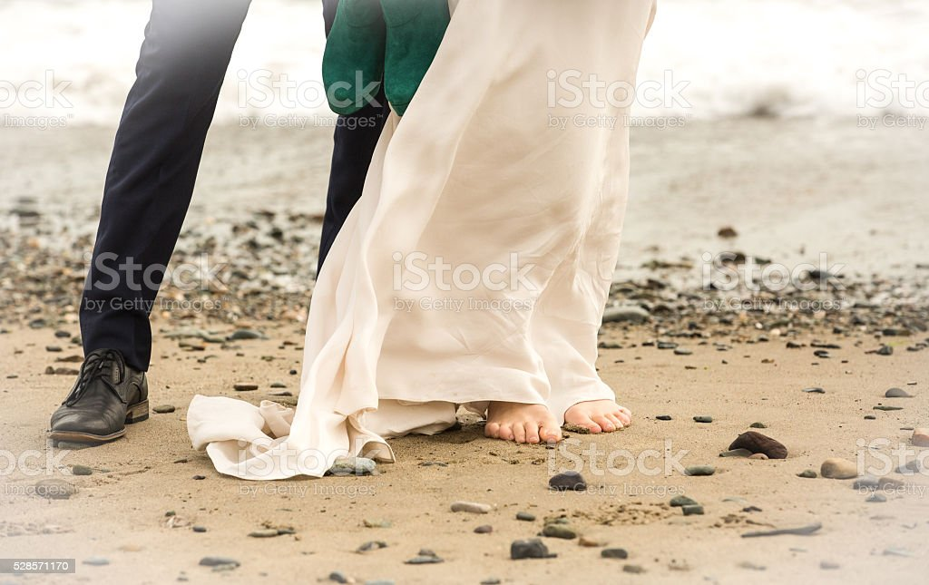 Wedding couple standing together on a beach bride bare foot stock photo