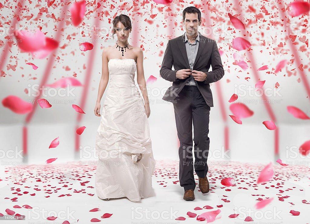 Wedding couple walking in roses royalty-free stock photo